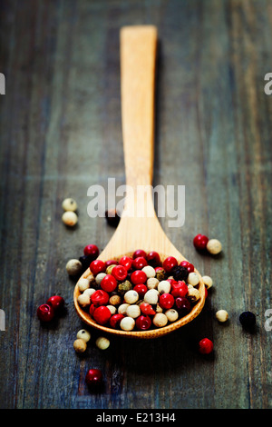 Peppercorn mix in wooden spoon - Stock Photo