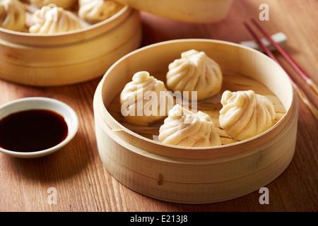 Baozi chinese dumplings on bamboo steamer - Stock Photo