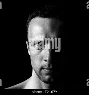 Young serious Caucasian man closeup portrait on black background - Stock Photo