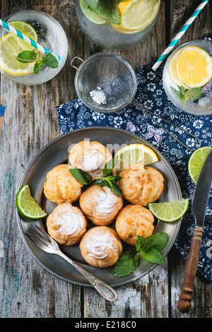 Vintage plate of homemade cakes profiteroles served with lemonade on old wooden table - Stock Photo