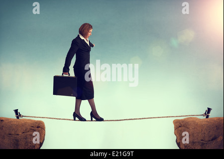 businesswoman balancing on a tightrope facing a challenge or risk or conquering adversity concept - Stock Photo