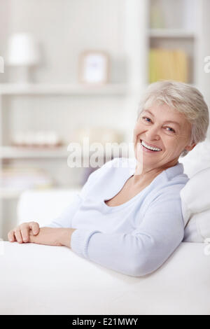Smiling elderly woman at home on the couch - Stock Photo