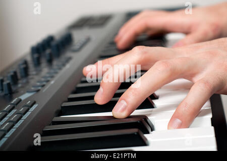 male hands playing the piano - Stock Photo