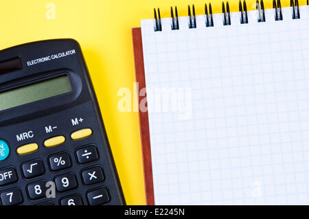 Notepad and calculator on yellow background. - Stock Photo
