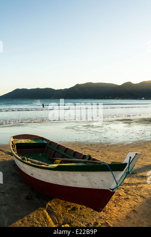 Boat on the sand and fisherman in the background at Pantano do Sul Beach. Florianopolis, Santa Catarina, Brazil. - Stock Photo