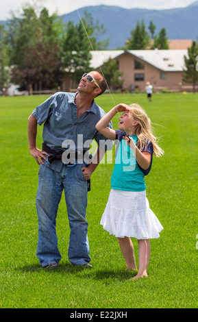 Father & young daughter flying a kite on a grassy field - Stock Photo