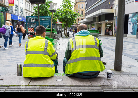 Two council workers who do street sweeping, having a coffee break. Sauchiehall Street, Glasgow, Scotland, UK - Stock Photo