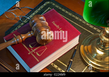 Judges wooden gavel on 'Family Law' book with scales of justice emblem illuminated by old desk lamp on leather bound - Stock Photo