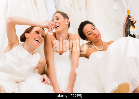 Brides drinking too much in wedding shop or store - Stock Photo