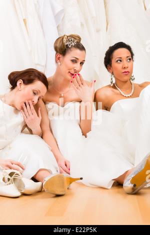 Brides drinking too much champagne in wedding shop - Stock Photo