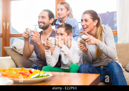 Family having leisure time together and playing with video game console - Stock Photo