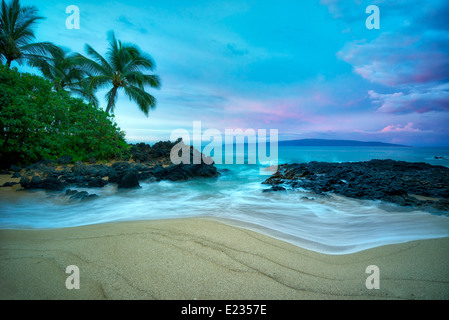 Secluded beach with palm trees and sunrise. Maui, Hawaii - Stock Photo