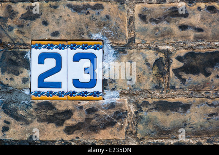 Close up of number 23 on a brick wall - Stock Photo