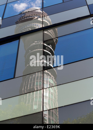 Telecom Tower against a blue sky with white clouds and trees. Distorted in window refections in Cubist manner - Stock Photo