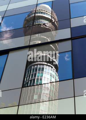 Telecom Tower against a blue sky with white clouds and trees Distorted in window refections in Cubist manner - Stock Photo