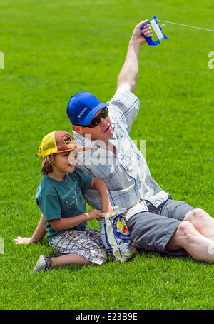 Father & young son flying a kite on a grassy field - Stock Photo