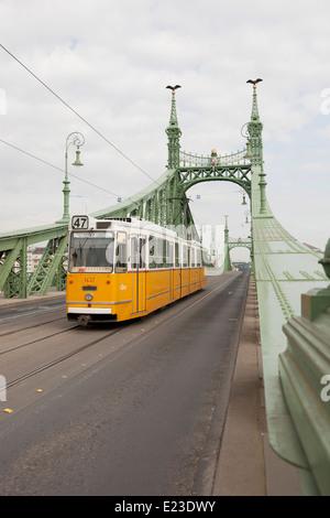Yellow tram crossing the Liberty Bridge in Budapest, Hungary - Stock Photo