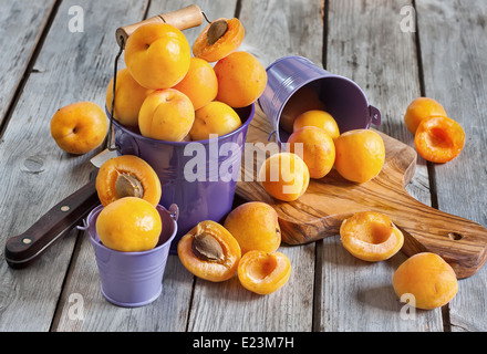 Sweet ripe apricots in small violet buckets. Selective focus. - Stock Photo