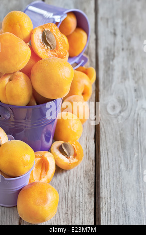 Sweet ripe apricots in small violet buckets. Selective focus. Copy space background. - Stock Photo