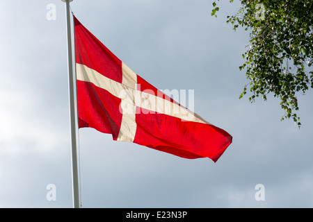 Danish flag on a flag pole in summer with gray clouds in the background - Stock Photo