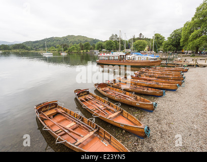 Wooden rowing boats lined up on the shore at Waterhead, Ambleside, Lake Windermere - Stock Photo