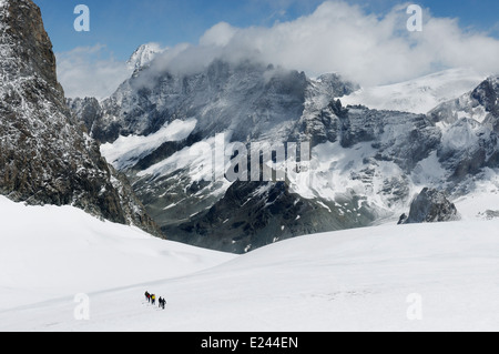 Figures of a mountaineering group high on Pigne d'Arolla near the Vignettes hut in the Swiss Alps - Stock Photo