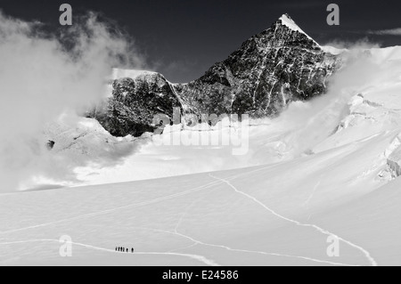 Figures of a mountaineering group high on Monte Rosa in the Swiss Alps, with Lyskamm beyond - Stock Photo