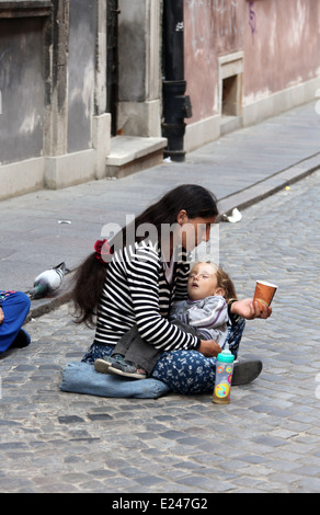 Woman begging with her child on the street in Warsaw - Stock Photo