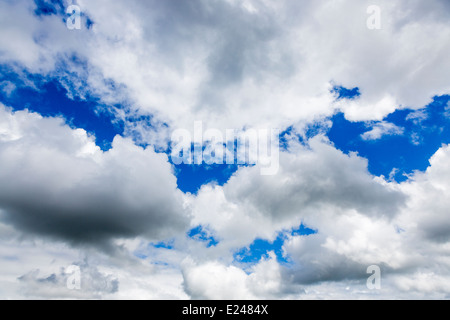 Fluffy white cumulus clouds turning grey against a blue sky background - Stock Photo