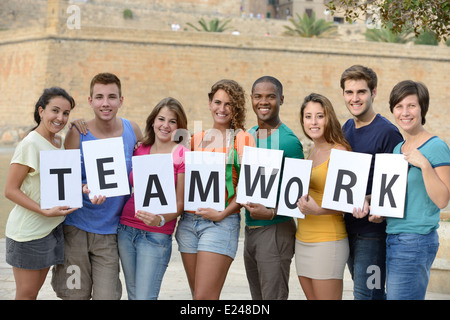 Group of young people holding teamwork sign smiling - Stock Photo