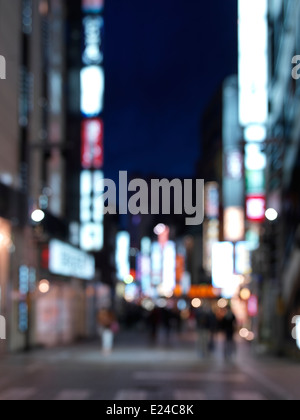 Out-of-focus street with bright signs, nighttime city scenery, Shinjuku, Tokyo, Japan. - Stock Photo