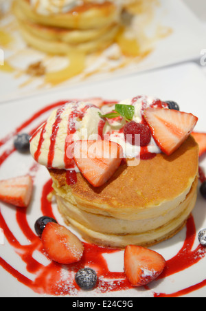 Pancakes with ice cream and fruits on a plate - Stock Photo