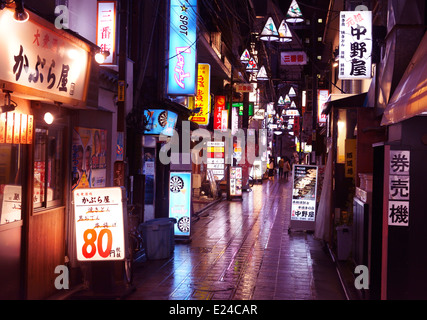 Narrow street filled with colorful restaurant signs at night in Nakano, Tokyo, Japan. - Stock Photo