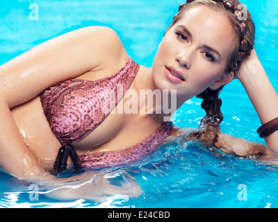 Beauty portrait of a young woman with braided long hair wearing a bikini lying in blue water - Stock Photo