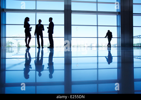 Silhouettes of several office workers standing by the window and talking - Stock Photo
