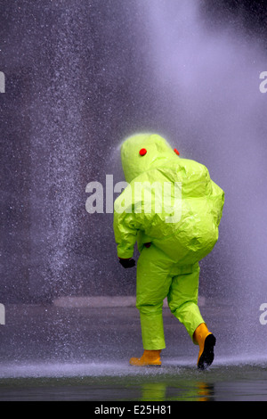 doctor with anti radiation suit during washing with powerful jets of water into the hazardous area contamination - Stock Photo