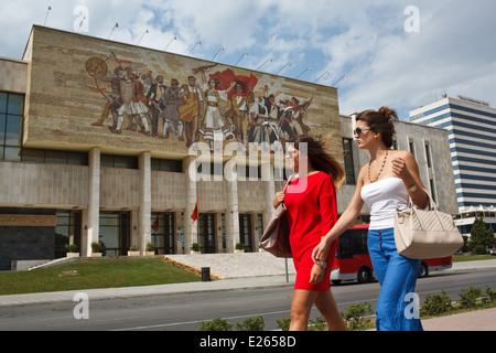 Two young fashionable women walk past National Historical Museum at Skanderbeg Square, Tirana, Albania. - Stock Photo