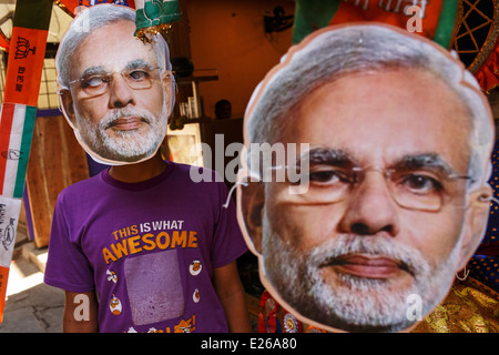 A young boy and masks with the current Indian prime minister Narendra Modi during 2014 general elections in Mumbai, - Stock Photo