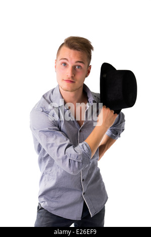 Handsome, cool, confident young man with top hat in hand, looking at camera - Stock Photo