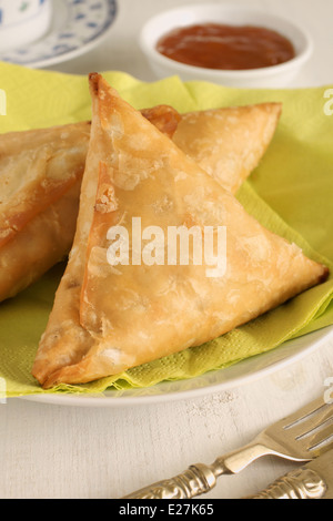 Samosas a spicy blend of vegetables or meat wrapped in a deep fried triangular pastry parcel - Stock Photo
