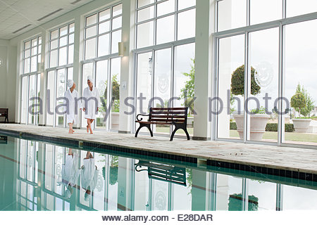Women in bathrobes walking along swimming pool at spa - Stock Photo