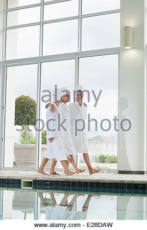 Women in bathrobes walking along swimming pool at spa - Stock Photo