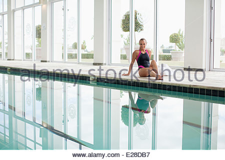 Portrait of smiling woman in bathing suit sitting poolside - Stock Photo