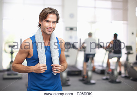 Portrait of smiling man with towel around neck in gymnasium - Stock Photo