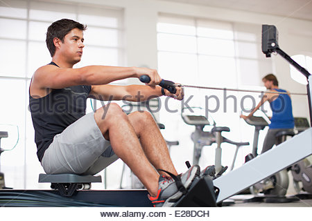 Young man exercising on rowing machine in gymnasium - Stock Photo