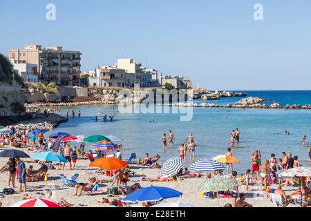 Beach parasols on a crowded sunny beach in summer sunshine on the coast at Otranto, Puglia, Salento region of southern - Stock Photo