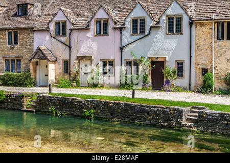 A row of pretty terraced cottages alongside the river Bybrook in the Cotswold village of Castle Combe in Wiltshire. - Stock Photo
