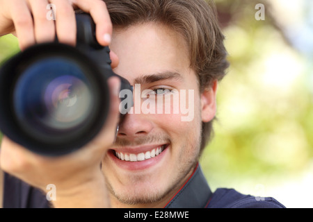 Front view of a photographer photographing with a dslr camera showing lens with a green background - Stock Photo