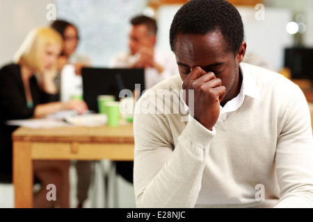 African American businessman tired in office - Stock Photo