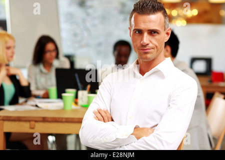 Portrait of thoughtful businessman with arms folded sitting in front of colleagues - Stock Photo
